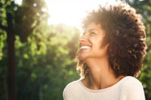 Close up side portrait of beautiful confident woman laughing in nature